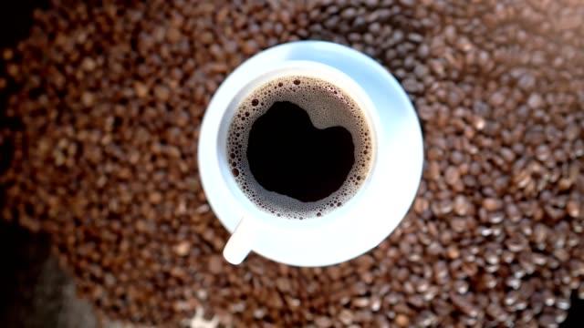eine nahaufnahme von einer in eine weiße tasse unter den braunen kaffeebohnen kaffee americano - koffeinmolekül stock-videos und b-roll-filmmaterial