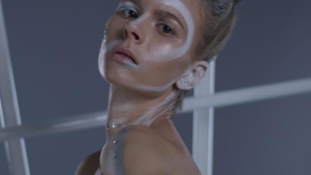 vidéos et rushes de gros plan d'un modèle angélique haute couture dans un maquillage de scène, montrant les expressions faciales. mode vidéo. - crayon à lèvres