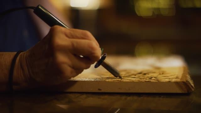 木材の断面に設計を書き込むペンの薪を使っているアーティストのクローズ アップ - 木目点の映像素材/bロール