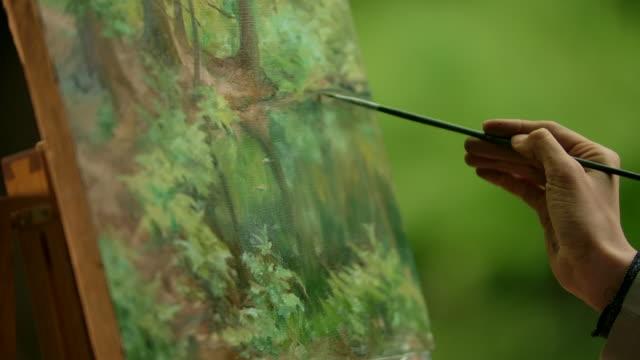 그림 위에 흐릿한 터치를 하는 브러시로 예술가의 손을 클로즈업 - 와이드 샷 스톡 비디오 및 b-롤 화면