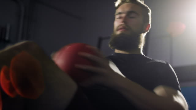 close-up of an attractive caucasian man in his twenties with a beard performs twisting ab/abdominal exercises with a medicine ball in a dramatically lit gym (medium tight shot) - skręcony filmów i materiałów b-roll
