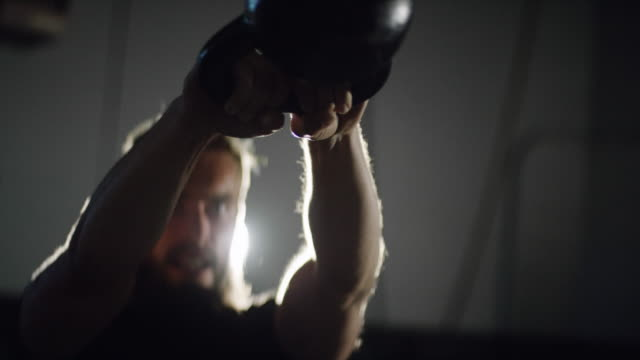 Close-Up of an Attractive Caucasian Man in His Twenties with a Beard Performing Kettlebell Swings in a Dramatically Lit Gym (medium shot)