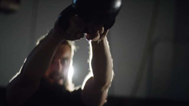 ひげを実行するケトルベル スイング劇的に点灯してジムで (ミディアム ショット) と彼の二十代の魅力的な白人男性のクローズ アップ - クロストレーニング点の映像素材/bロール