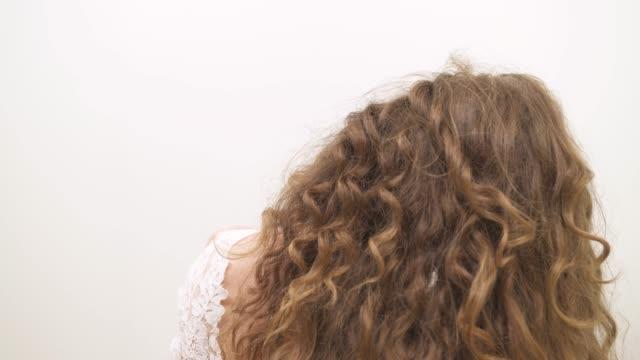 stockvideo's en b-roll-footage met een close-up van een aantrekkelijke vrouw met prachtige lang krullend haar staande keerde terug naar de camera, draaien haar hoofd en glimlachend - blond curly hair
