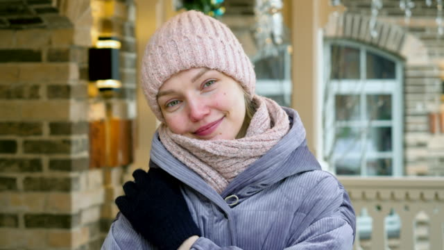 Close-up of an attractive young smiling girl looking at camera in winter outdoor. 4K Christmas holidays. Portrait of young happy woman smiling and looking at camera in winter outdoor. 4K russian culture stock videos & royalty-free footage