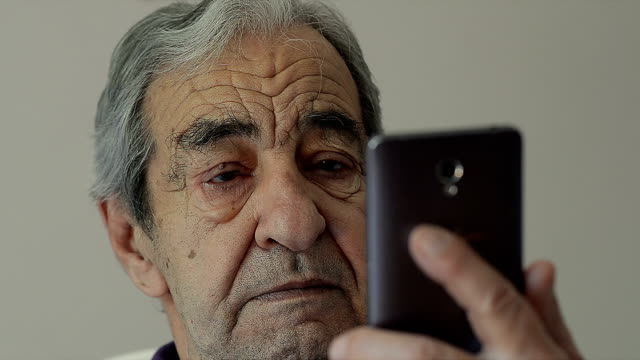 Closeup of an Old Man Reads SMS on a Mobile Phone video
