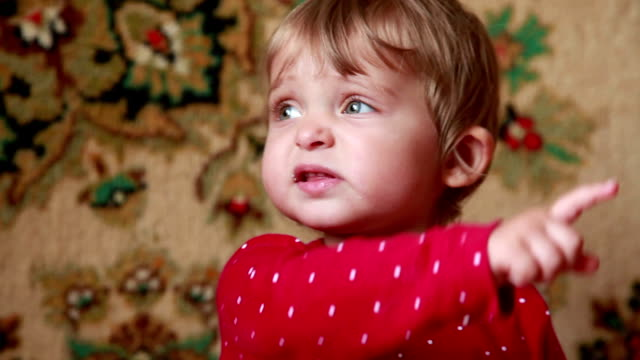 Close-up of an unhappy baby girl pointing to the right Baby pointing to the right side, selective focus pointing stock videos & royalty-free footage