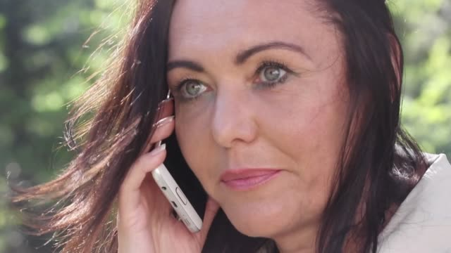 Close-up of an upset mature woman talking on the phone A close-up shot of a mature woman speaking on her mobile phone, looking upset. donna stock videos & royalty-free footage
