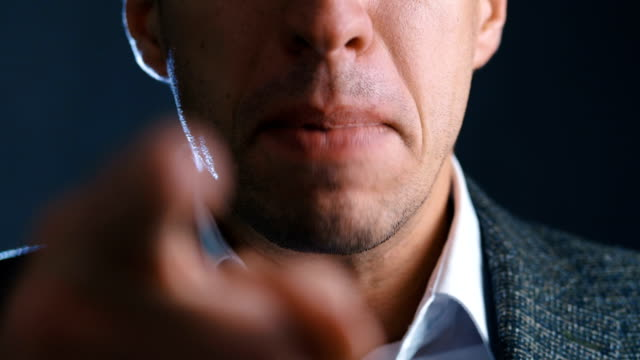 Close-up of angry boss scolding and shouting at employees threatening with a finger and shouting aggressively at the camera.