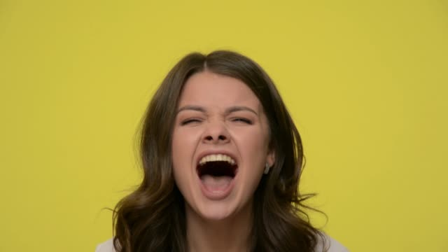 Closeup of angry brunette woman shouting with wide open mouth, showing rage and frustration, screaming aggressively Closeup of angry brunette woman shouting with wide open mouth, showing rage and frustration, screaming aggressively, being pissed off yelling long and loud. studio shot isolated on yellow background mouth open stock videos & royalty-free footage