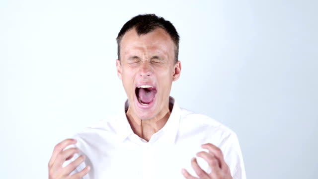 Close-up of angry businessman screaming against blue background video
