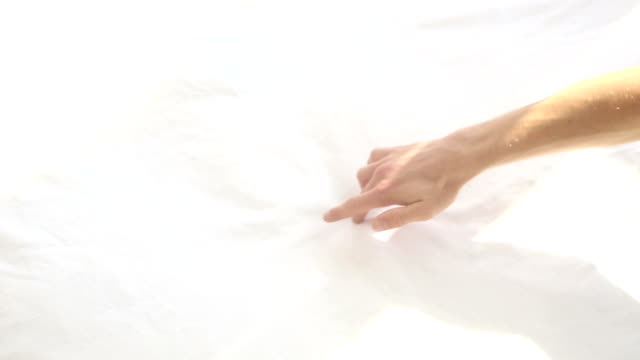 closeup of arm of woman drawing a heart on white bedsheets with finger video