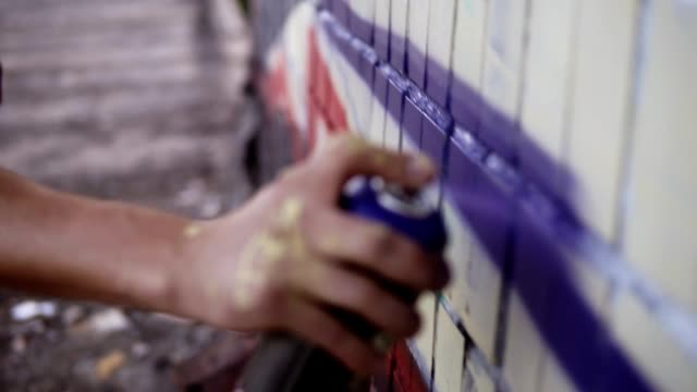 Close-up of artists hand dirty in paint applying spray drawing a blue coloured lines on a street building wall. Action. Stained fingers of artist hold spray can with colored paint on concrete wall. Street artist in process of creating graffiti