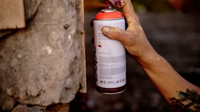 Close-up of artists hand dirty in paint applying spray drawing a red coloured line on a street building bricked wall. Action. Stained fingers of artist hold spray can with colored paint on concrete wall