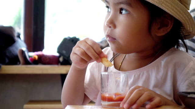 Close-up of Asia children eat french fries, slow motion shot. ビデオ