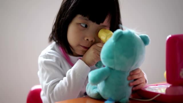 vídeos de stock e filmes b-roll de plano aproximado de asiático chinês criança pequena jogar fingir médico com o urso de pelúcia - teddy bear