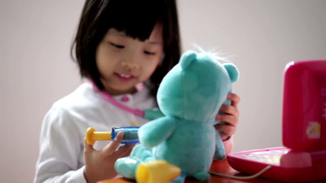 Closeup of Asian chinese toddler playing pretend doctor with her teddy bear Closeup of Asian chinese toddler playing pretend doctor with her teddy bear. Pretend injection with a toy syringe. dressing up stock videos & royalty-free footage