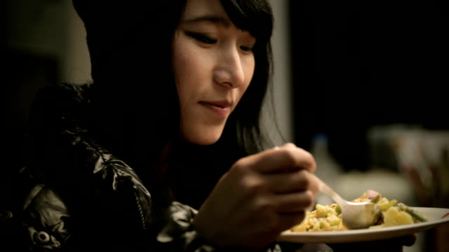 Close-up of Asian girl enjoying tasty and healthy food. Indoor low key, close-up, zooming and panning video of an Asian late teen serene girl eating, enjoying tasty and healthy food. She is in a black jacket and black woolen cap. One person horizontal composition with selective focus and copy space. tasting stock videos & royalty-free footage