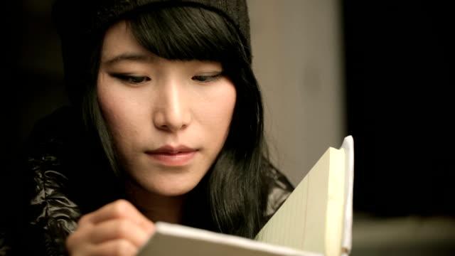 asyalı kız öğrenci bir defterde yazılı close-up. - çalışma kitabı stok videoları ve detay görüntü çekimi