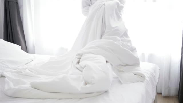 closeup of asian woman throwing white blanket on bed - stock video - kołdra filmów i materiałów b-roll