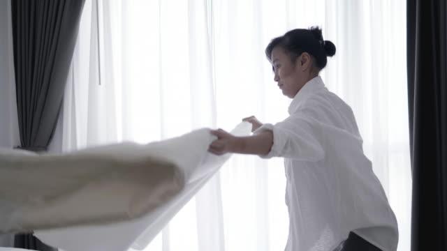 Nahaufnahme der Asiatin werfen weiße Decke auf Bett - Stock video – Video