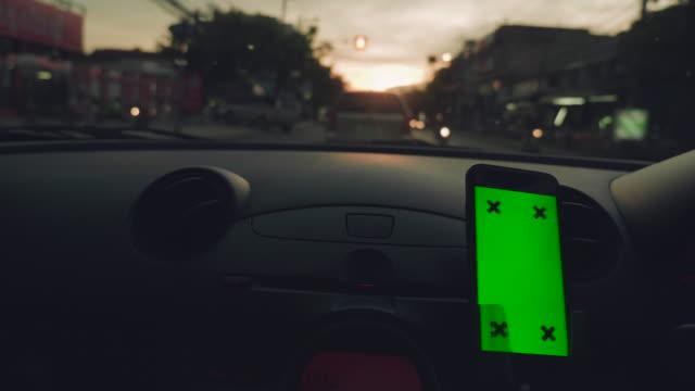 Close-up van Aziatische vrouw met behulp van smartphone in de auto, groen scherm video