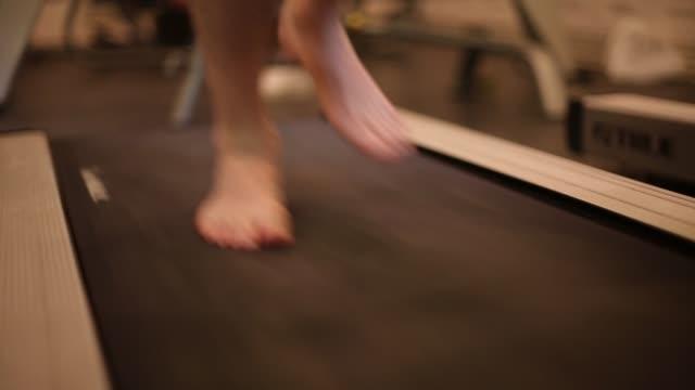 Closeup of athlete's feet running on treadmill barefoot video
