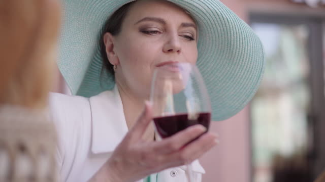 Close-up of attractive mid-adult Caucasian woman in elegant hat drinking red wine while reading. Portrait of elegant beautiful lady enjoying sunny summer day outdoors. Leisure, hobby. Close-up of attractive mid-adult Caucasian woman in elegant hat drinking red wine while reading. Portrait of elegant beautiful lady enjoying sunny summer day outdoors. Leisure, hobby. one mid adult woman only stock videos & royalty-free footage