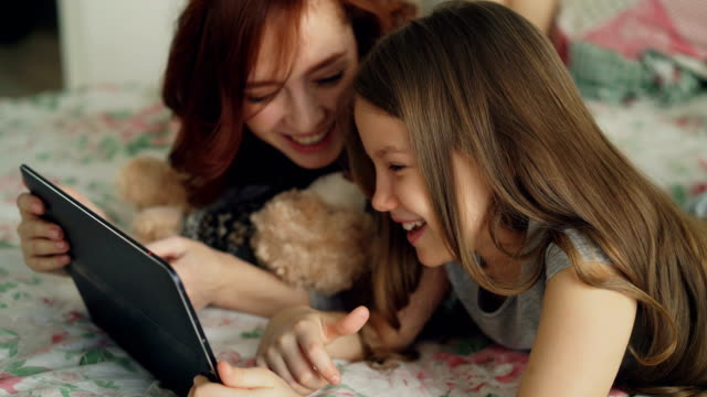 close-up of attractive young mother and her cute daughter in pajamas laughing and looking in digital tablet while lying on bed at home in the morning - tablet stock videos and b-roll footage