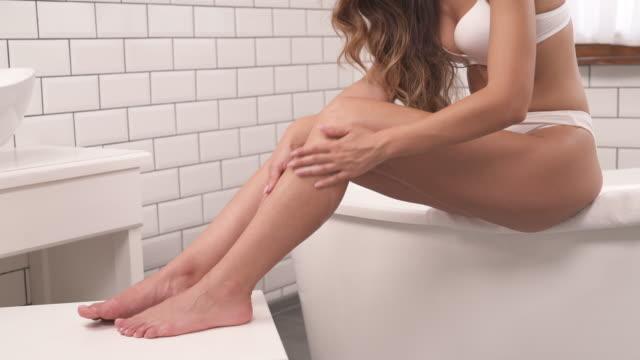 stockvideo's en b-roll-footage met close-up van aantrekkelijke jonge vrouw in stijlvolle interieur badkamer toepassing vochtinbrengende lotion in de huid van haar benen. mooi meisje het verzorgen van haar lichaam - menselijk been