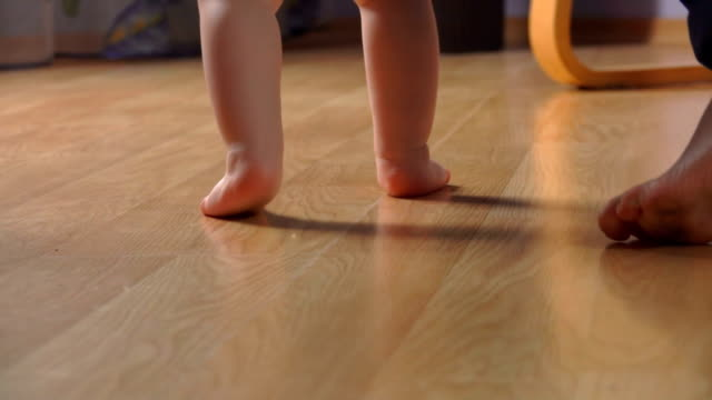 Close-up of baby feet taking the first steps Close-up of baby bare feet taking the first steps next to mother first occurrence stock videos & royalty-free footage