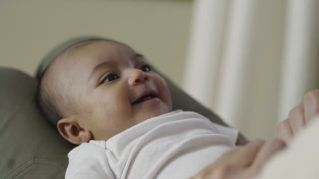 Close-up of baby smiling as her father plays with her feet