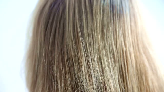 closeup of backside of head with long hair being combed - spettinato video stock e b–roll