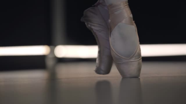 Close-up of ballerina's feet in pointes balancing on tiptoes. Professional female ballet dancer practicing. Lifestyle, art, elegance, choreography. Close-up of ballerina's feet in pointes balancing on tiptoes. Professional female ballet dancer practicing. Lifestyle, art, elegance, choreography. ballet dancer stock videos & royalty-free footage