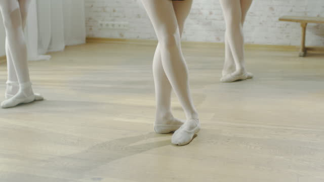 Close-up of Ballet Dancer's Legs, Practicing Their Dance in Pointe Shoes on a Wooden Floor. Shot on a Sunny and Bright Day in a Modern Studio. In Slow Motion. video