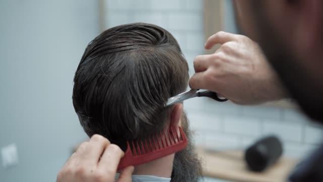 vidéos et rushes de gros plan du coiffeur coupe les cheveux de ciseaux au salon de coiffure. mains de salon de coiffure au processus de travail. coiffeur coupe de cheveux faisant d'homme barbu attrayant en salon de coiffure. salon de coiffure au travail. salon de beauté. - salons et coiffeurs