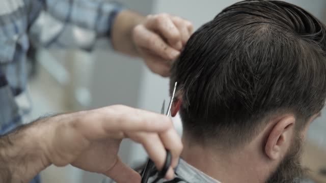 Close-up of barber cuts the hair by scissors at barbershop. Hairdresser's hands at working process. Barber making haircut of attractive bearded man in barbershop. Hairdresser at work. Beauty saloon. Close-up of barber cuts the hair by scissors at barbershop. Hairdresser's hands at working process. Barber making haircut of attractive bearded man in barbershop. Hairdresser at work. Beauty saloon hairstyle stock videos & royalty-free footage