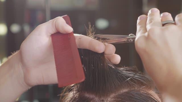 床屋のクローズ アップは、スローモーションで理髪店にはさみで髪の毛をカットします。 - 美容院点の映像素材/bロール