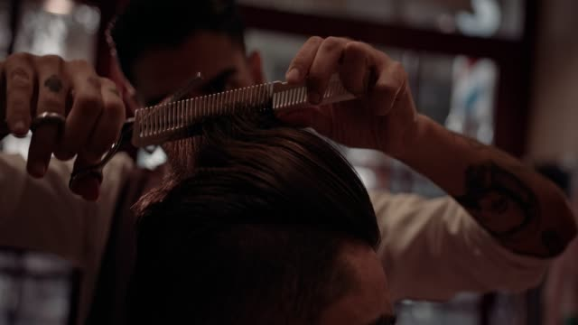 Close-up of barber's hands cutting man's hair in barber shop video