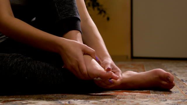 Closeup of barefoot young woman massaging her sprained foot having painful symptoms video