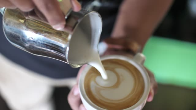 Close-up of Barista adding foamy milk into a cup of coffee