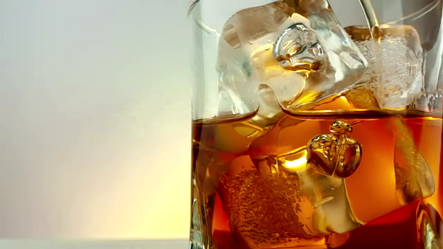 close-up of  barman pouring whiskey in the drinking glass with ice cubes on warm white background, time of relax drink with whisky video