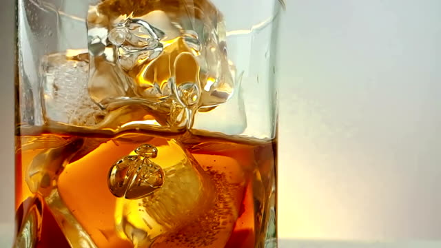close-up of  barman pouring whiskey in the drinking glass with ice cubes on warm white background, time of relax drink with whisky close-up of  barman pouring whiskey in the drinking glass with ice cubes on warm white background, time of relax drink with whisky, shot in slow motion bottle stock videos & royalty-free footage