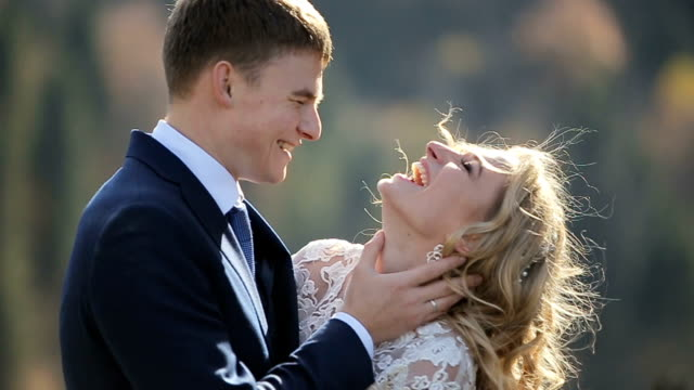 Close-up of Beautiful bride and groom gently hugging in the mountains video