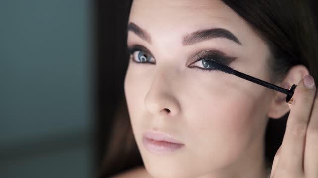 stockvideo's en b-roll-footage met close-up van mooie charmante jonge kaukasische vrouw die wimpers verven - eyeliner