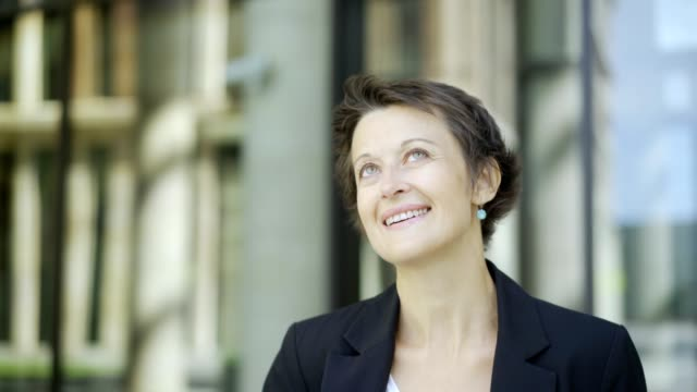 Close-up of beautiful middle adult woman in black jacket day dreaming and smiling while waiting for somebody outdoors. Woman looking serene, stress less and happy. Copy space to the left Close-up of beautiful middle adult woman in black jacket day dreaming and smiling while waiting for somebody outdoors. Woman looking serene, stress less and happy. Copy space to the left anticipation stock videos & royalty-free footage