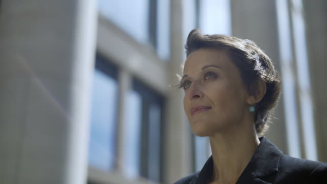 Close-up of beautiful middle aged woman standing outdoors and looking confidently away while looking for somebody, her short hair waving in wind