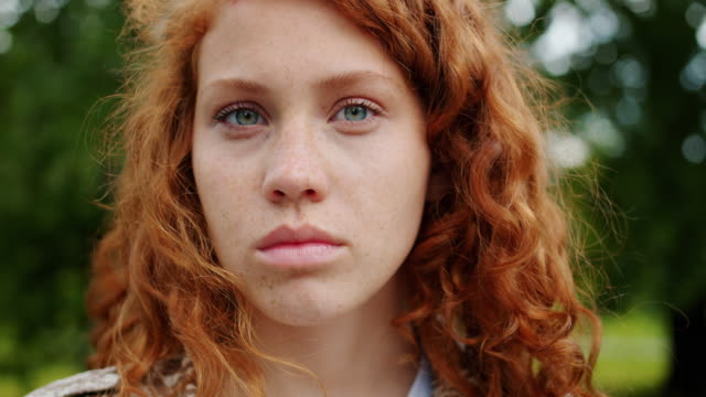 Close-up of beautiful redhead teenager looking at camera with serious face Close-up portrait of beautiful redhead teenager looking at camera with serious face standing outdoors in park. Lifestyle, emotions and people concept. redhead stock videos & royalty-free footage