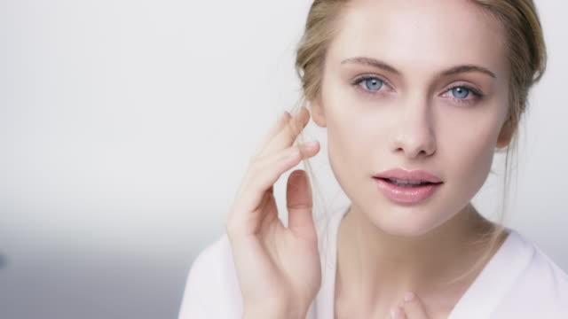 彼女の顔に触れる美しい内気な女性のクローズ アップ - スキンケア点の映像素材/bロール