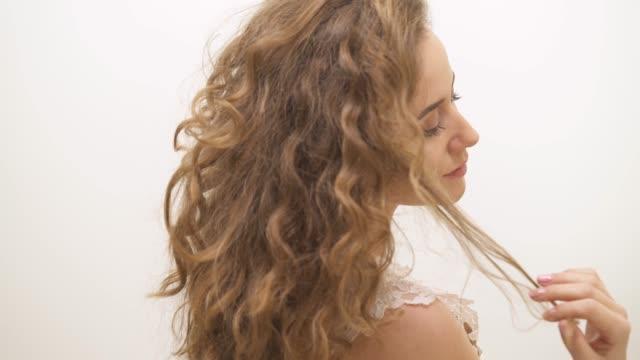 stockvideo's en b-roll-footage met een close-up van mooie vrouw met lang krullend haar staan keerde terug naar de camera, draaien haar hoofd en het aanraken van het slot van haar haar - blond curly hair